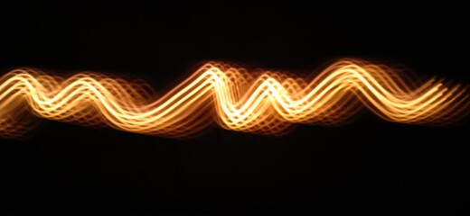 Closeup of Golden yellow Neon light wave pattern abstract flowing through the isolated black background made with long exposure , light painting technique . Copy space .