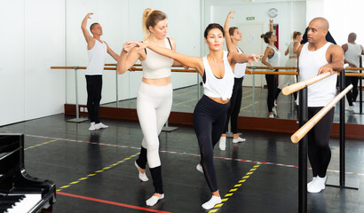 European female ballet teacher showing moves in front of a group of multiracial ..dancers in large dancing studio