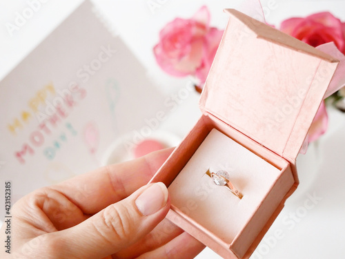 Box with beautiful  ring and roses on white background, closeup, mother's day concept