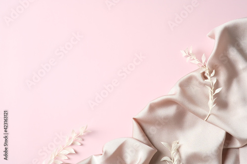 Silk and flowers on pink background. Flat lay, top view. Mother's Day greeting card template.