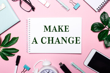 MAKE A CHANGE is written in a white notebook on a pink background surrounded by business accessories and green leaves.