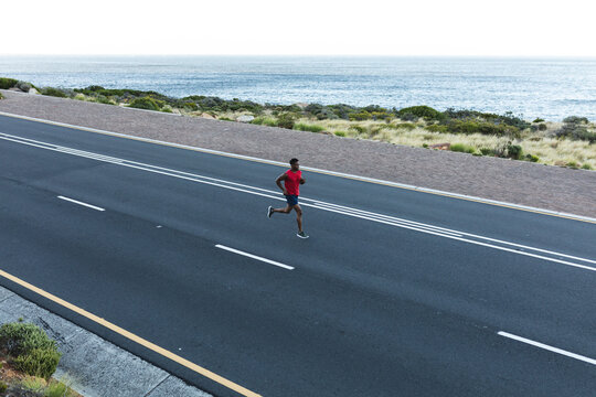 African american man exercising outdoors running on a coastal road