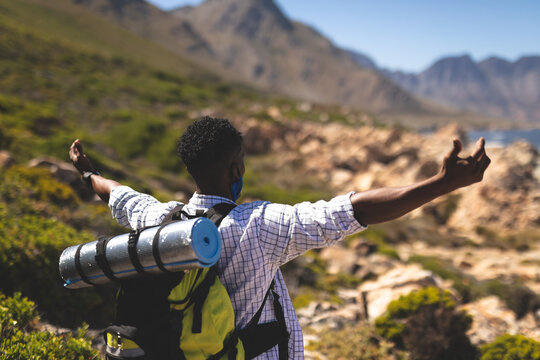 Portrait of fit african american man hiking outdoors in countryside to camera