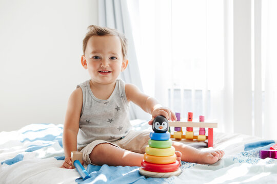 Cute baby toddler playing with learning toy pyramid stacking blocks at home. Early age Montessori education. Kids hand brain fun development activity for preschoolers.