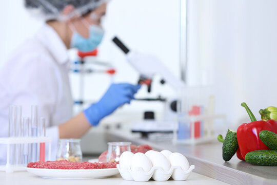 Different food on table and scientist proceeding quality control in laboratory