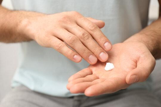 Man applying cream onto hand on blurred background, closeup