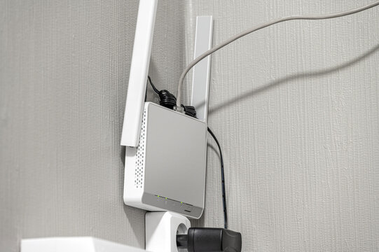 Wifi router on the wall, plugged to the network with utp cable