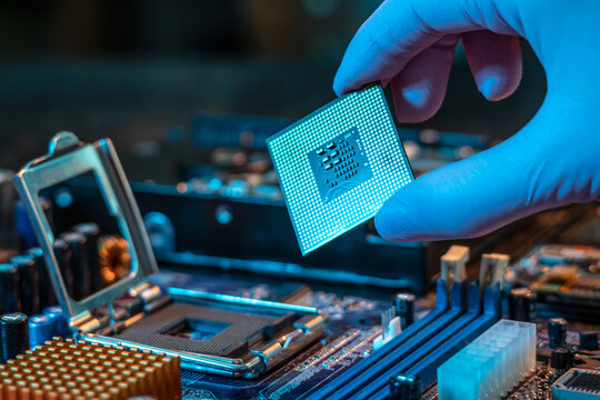 Engineer's gloved hand is holding the CPU chip on the background of the motherboard. High-tech hardware microelectronics