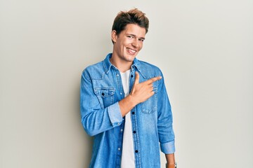 Fototapeta Handsome caucasian man wearing casual denim jacket smiling cheerful pointing with hand and finger up to the side