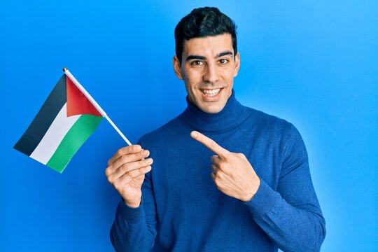 Handsome hispanic man holding jordania flag smiling happy pointing with hand and finger
