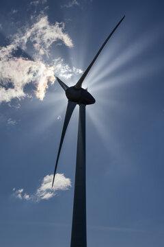 Black silhouet windturbine with backlight and sunrays