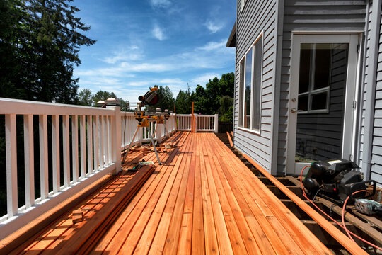 Complete home outdoor deck remodel with new red cedar wooden boards being installed