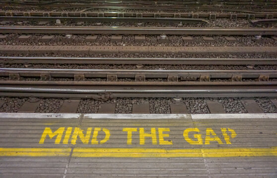 Yellow warning mind the gap sign on the platform in London
