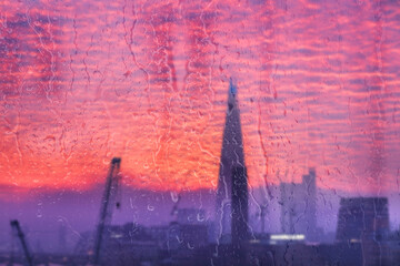 Beautiful landscape concept view of London City through glass window with streaks of rain and raindrops running down the glass