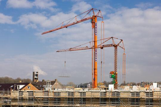Mobile tower cranes at construction site apartment building Dutch village