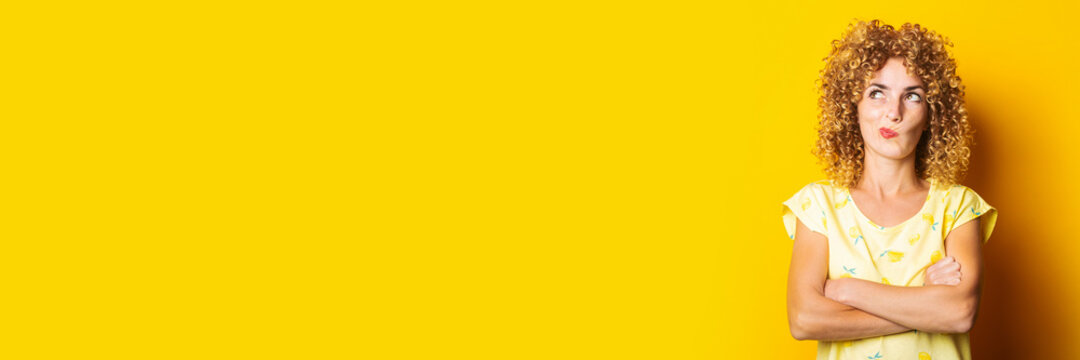curly young woman with her arms crossed looks thoughtfully upwards on a yellow background. Banner.