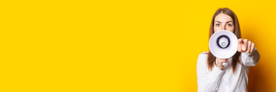 Friendly young woman holds a megaphone in her hands and points her finger at the viewer on a yellow background. Hiring concept, help wanted. Banner