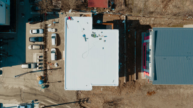 Aerial view of an apartment building with flat roof in construction, ballasted system with geotextile, PVC or EPDM membrane