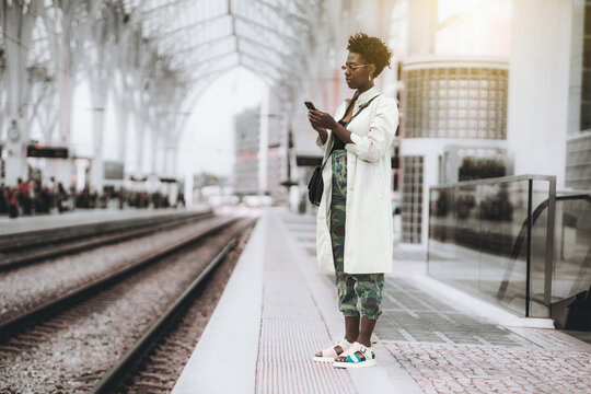 A young fancy curly-hair African woman in sunglasses, white trench, and camouflage trousers is phoning while standing on the platform of a railroad station depot and waiting for the train to travel