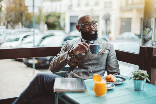 A fancy bearded hairless senior entrepreneur in glasses and a stylish custom-made costume, is sitting in an outdoor cafe in the morning and drinking a delicious coffee and pensively looking aside