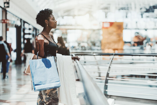 A beautiful young elegant black woman is standing next to the railing of a modern shopping mall with disposable paper bags with purchases in her hand after shopping; a copy space place on the right