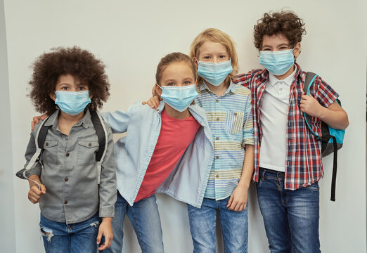 Cheerful diverse children wearing protective face masks looking at camera, posing together over light background