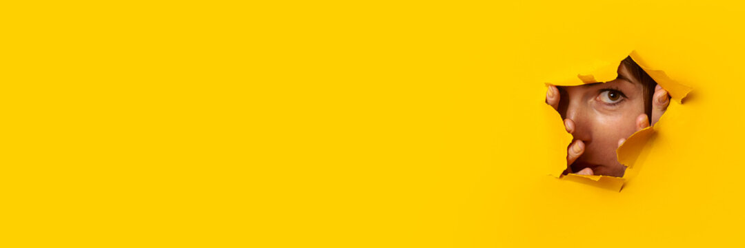 Young woman peeks out of a hole in the wall on a yellow background. Banner