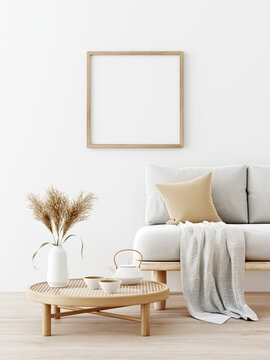 Square poster mockup with wooden frame in living room interior with sofa, beige pillow, dried Pampas grass on caned table and Japandi style decor on empty wall background. 3D rendering, illustration