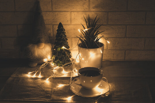 Christmas decoration and a leprechaun in the candlelight, a cup of coffee among Christmas decorations