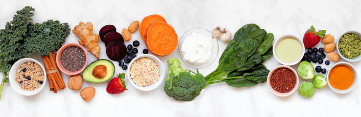 Set of healthy food ingredients. Top view table scene on a white marble banner background. Super food concept with green vegetables, berries, whole grains, seeds, spices and nutritious items.