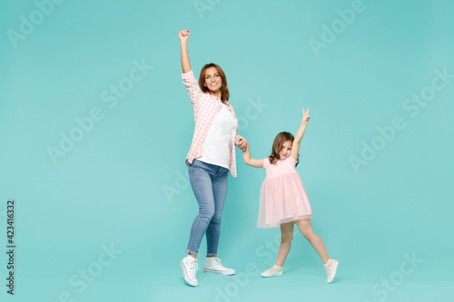 Full length happy woman in pink clothes have fun with cute child baby girl 5-6 years old. Mommy little kid daughter dancing isolated on pastel blue background studio. Mother's Day love family concept.