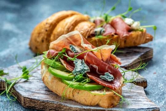 Croissant sandwich with jamon ham serrano paleta iberica, blue cheese, avocado, microgin on blue background. Food recipe background. space for text. top view