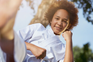 Cheerful Afro American girl practicing martial arts outdoors