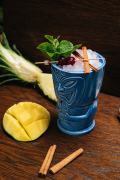 Refreshing cold Tiki Drink Cocktail with pineapple, mango, mint and cinnamon