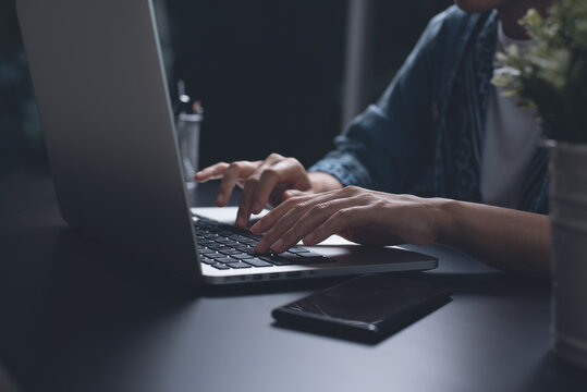Business woman hands typing, overtime working on laptop computer from home at night