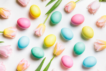 Easter layout of light pink and yellow spring flowers tulips and pastel colors eggs on a white background. Festive flat lay, happy easter concept.