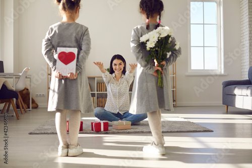 Happy birthday or mother's day. Two daughters stand with their backs to the camera and hold flowers and a handmade postcard. Mom sits on the floor with outstretched arms wanting to hug children.