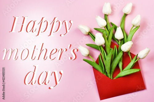 Red envelope full of white tulips with an inscription HAPPY MOTHER'S DAY on pink background. Mother's day concept. Greeting postcard. Flat lay. Creative composition.