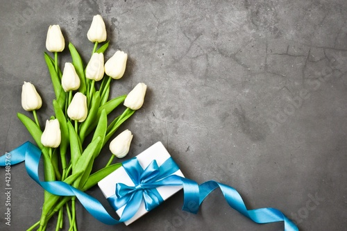 White Tulip bouquet with blue ribbon and gift present on gray background. copy space, flat lay. Greeting card. Happy mother's day, valentines day, happy birthday, happy father's day concept.