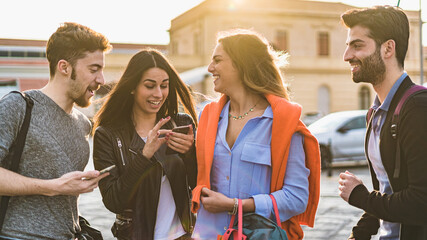 Two couple of millennials, young people having fun talking together and using mobile smartphone...