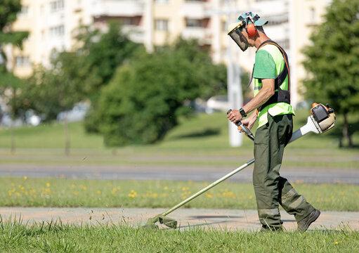 Municipal gardener landscaper man worker cutting grass with string trimmer machine along city street