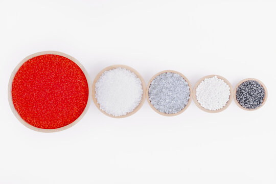 Polymer products of different colors in containers on a white background.Polymers and polystyrene.Chemical industry.Inorganic and organic,amorphous and crystalline substances,high molecular compound