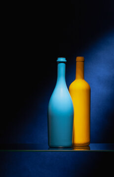Two empty wine bottles on the glass table in the dark bar.
