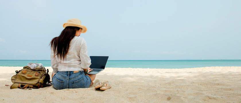Asian woman with bagpack sitting on sand at beach using laptop computer working