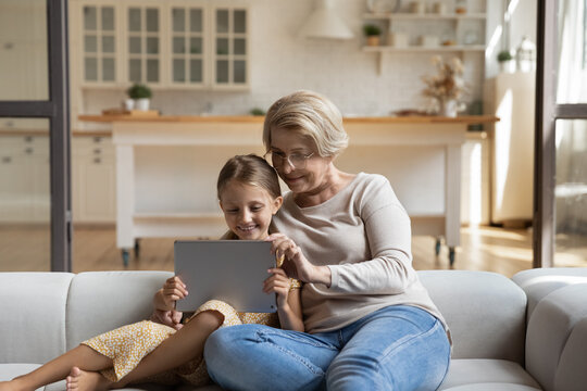 Happy loving elderly Caucasian grandmother and 7s granddaughter relax on sofa in living room using tablet together. Smiling mature granny and small girl child have fun with pad. Technology concept.