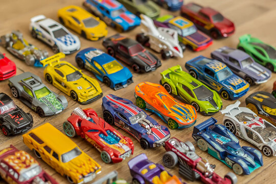 Ivanovo, Russia - June, 2019 : The group of colorful toy car collection on wooden background. Hot Wheels. Top view. Selective focus.