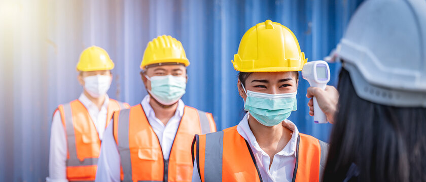 Engineers wearing face masks line up for temperature check before entering workplace.  Coronavirus pandemic. Social distancing.