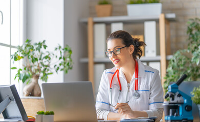 doctor is talking with somebody by laptop