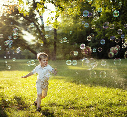 Cute little boy chasing soap bubbles