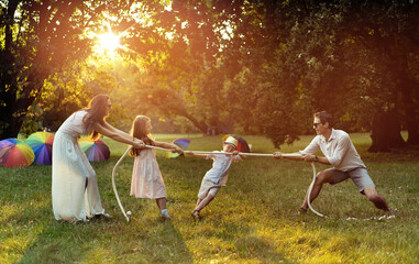 Joyful family playing tug-of-war in the park